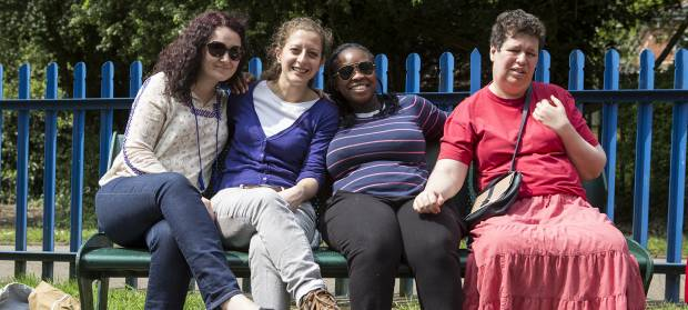 Group of people sat outside in sunshine on a bench in front of a playpark